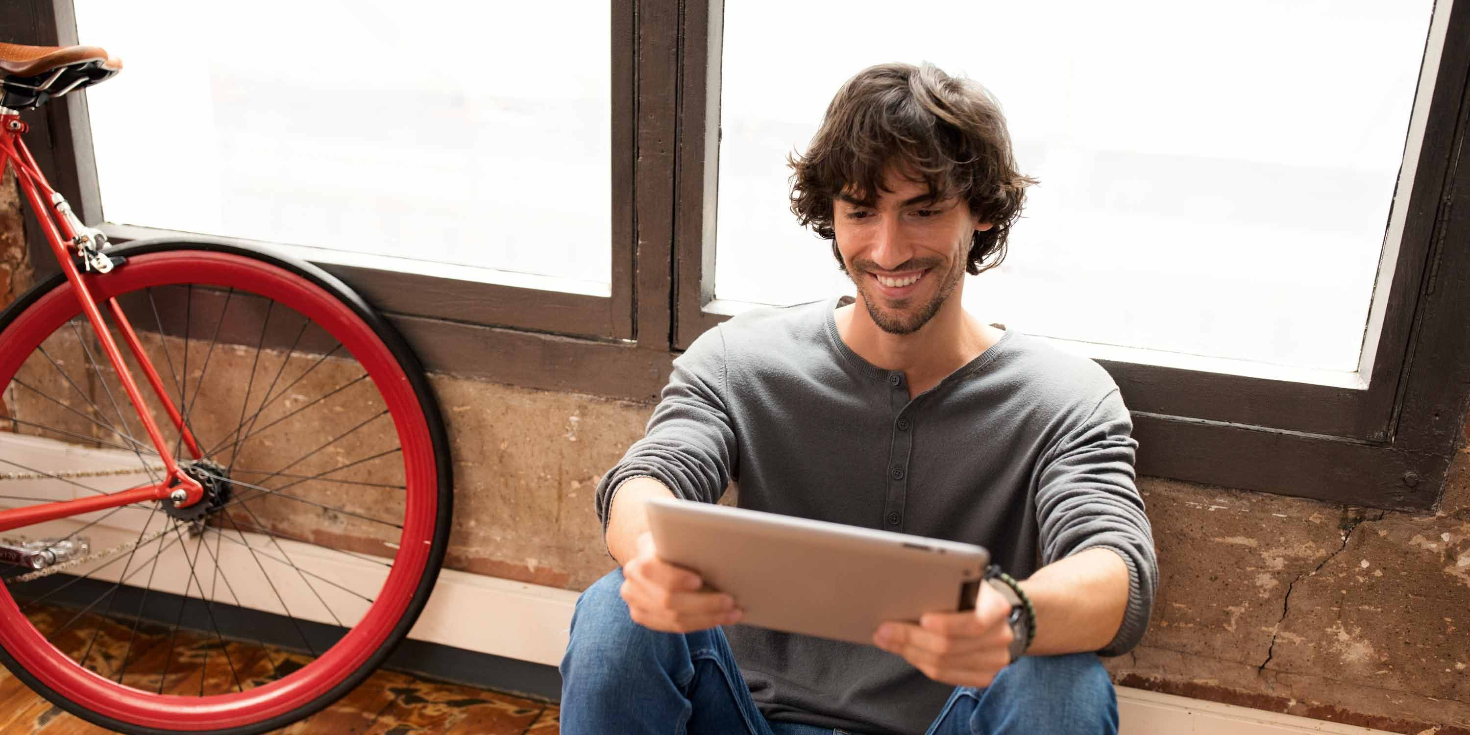 Man sitting in front of window with tablet stage